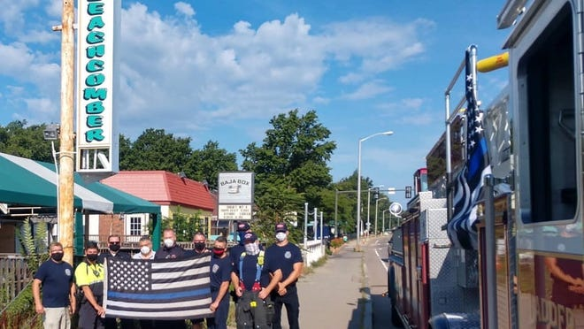 A 'Thin Blue Line' flag first flown on a Hingham Fire Truck made its way through Quincy this weekend, where it was greeted by Cindy Chesna and Mayor Thomas Koch. Friends Of Quincy Firefighters IAFF Local 792 photo