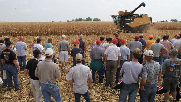 Spectators watch a combining demonstration  at the 2010 Farm Progress Show near Boone.