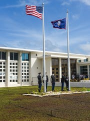 In this Dec. 22 file photo, Guam National Guard members raise the American and Guam flags at the former Guam Congress building in Hagåtña.