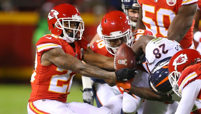 Chiefs cornerback Marcus Peters (22) strips the ball away from Broncos running back Jamaal Charles (28) during the first half in Kansas City.