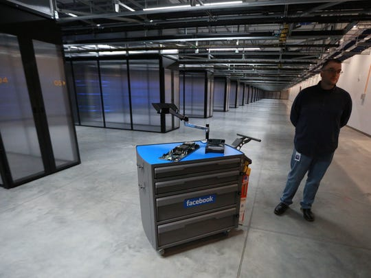 A Facebook data center technician stands next to a work station inside the new Facebook data center on Friday, Nov. 14, 2014, in Altoona, Iowa.
