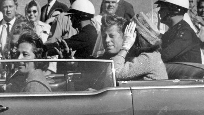 President John F. Kennedy, with Jacqueline Kennedy to his left, waves from his car in a motorcade in Dallas on Nov. 22, 1963.