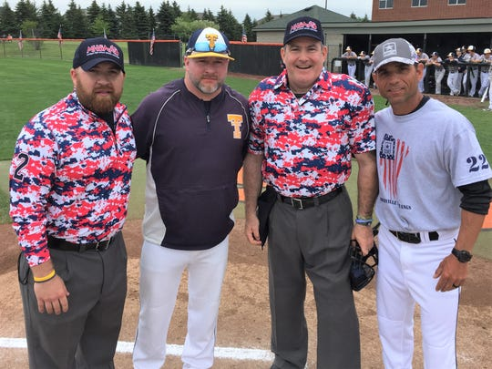 Umpires Mike Traicoff (far left) and Jeff Metz (third