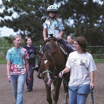 Volunteers help a rider during a session at Jeremiah's Crossing in Babcock. Jeremiah's Crossing, a nonprofit therapeutic horseback-riding ranch for children and adults with diagnosed physical, cognitive, emotional and academic special needs, is a partner program of the United Way of Inner Wisconsin and the Marshfield Area United Way