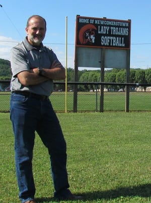 Charles Lenzo of Lenzo Studio Photography of Newcomerstown is pictured in front of a new sign that he purchased to help promote the Lady Trojans softball team. Photo by Ray Booth