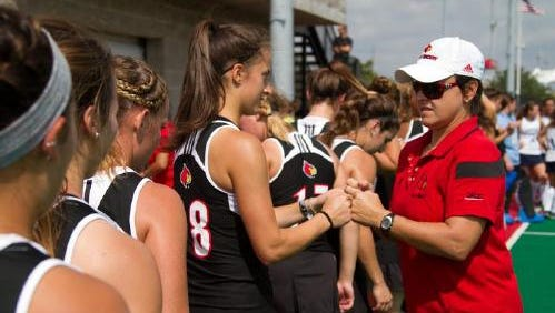 U of L field hockey head coach Justine Sowry gives knuckles to Shannon Sloss (8) before the start of a game against North Carolina on Sept. 20, 2014.