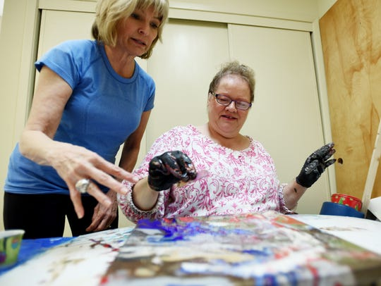 Laura Core, left, helps Laurie Baker with a painting