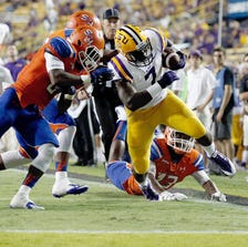 BATON ROUGE, LA - SEPTEMBER 06:  Leonard Fournette #7 of the LSU Tigers is pushed out of bounds by Andre Moseley #29 and Earnest Payton #13 of the Sam Houston State Bearkats during the fourth quarter of a game at Tiger Stadium on September 6, 2014 in Baton Rouge, Louisiana.  LSU won the game 56-0. (Photo by Stacy Revere/Getty Images)