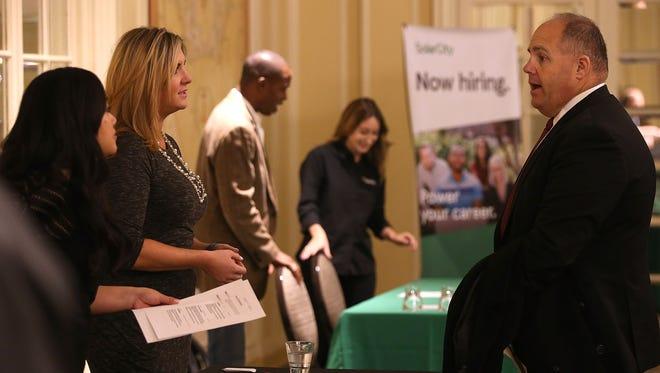 A job seeker (R) meets with recruiters during a career fair in San Francisco. The Labor Department releases the May jobs report on Friday.
