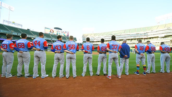 The Rangers stand for the National Anthem before a game against the A's.