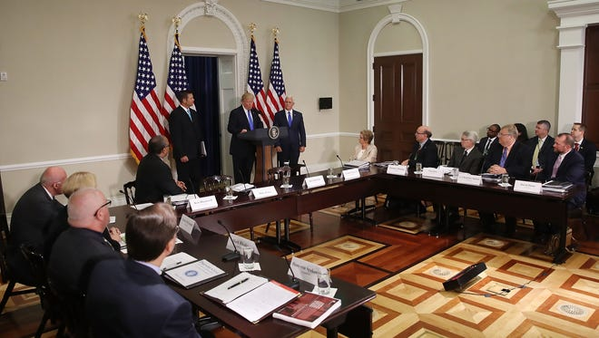 President Trump speaks while flanked by Kansas Secretary of State Kris Kobach and Vice President  Pence during the first meeting of the Presidential Advisory Commission on Election Integrity in the Eisenhower Executive Office Building on July 19, 2017.