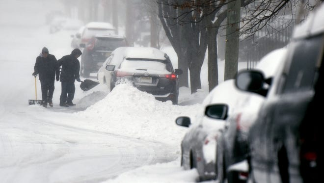 Paul and Paola Nores dig out their car in Clifton on Tuesday, March 14, 2017.