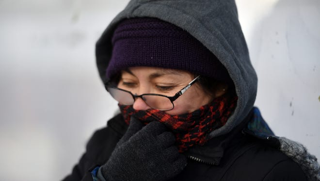 With temperatures dipping a woman tries to stay warm in a bus shelter on Ellison Street in Paterson on Tuesday afternoon.