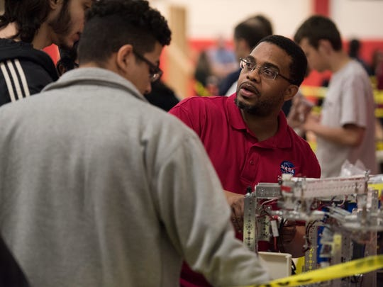 Karream Sheard talks with teammates during a robotics competition at Passaic County Community College in Paterson in May.