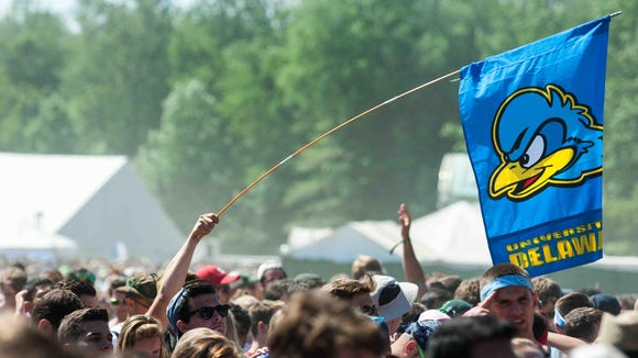A fan holds up a University of Delaware flag before Weezer perfoms at the Firefly Music Festival in June.