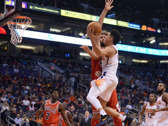 Suns guard Devin Booker goes up for a shot against Bulls center Robin Lopez during Sunday's win.