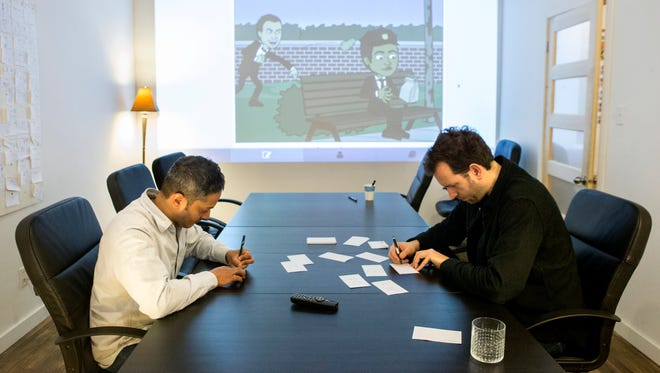 In this Dec. 2013 photo, Bitstrips CEO and Creative Director Jacob Blackstock, right, and co-founder Shahan Panth draw cartoons as part of a brain storming process at the company's offices in Toronto. Bitstrips, a mobile application that helps people turn their lives into comic strips, may seem like a sudden sensation now that its vignettes are all over Facebook and other social networks. But the Toronto startupís success has been a drawn-out process.