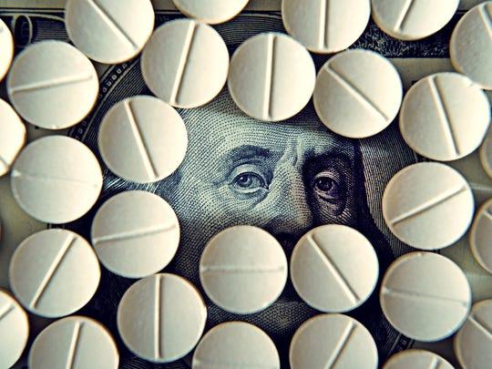 Prescription drug tablets covering a hundred dollar bill, with Ben Franklin's eyes poking through.