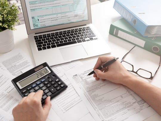 Person filling out paper tax form while typing on calculator