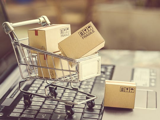 A miniature shopping cart full of boxes sitting on top of a laptop.