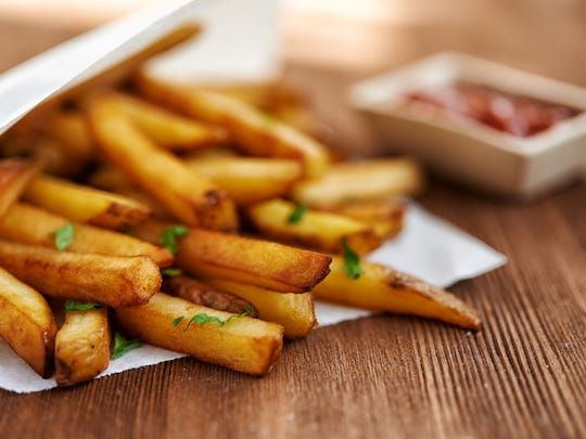 Close-up shot of some golden brown french fries, sprinkled with dill. In the background, you see an out-of-focus ketchup container.