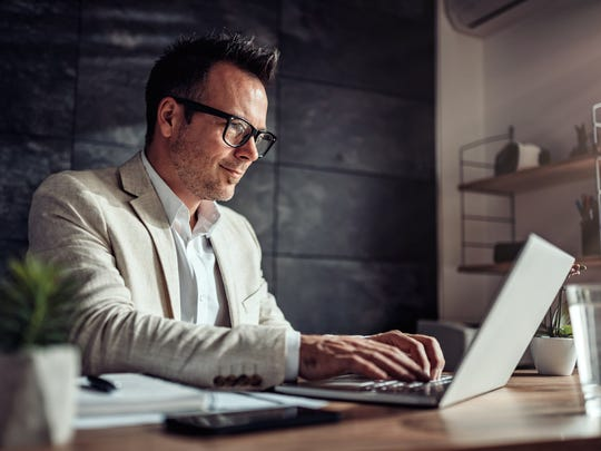 A man uses a laptop at a desk.