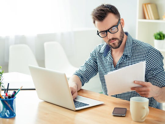 Man typing on laptop with one hand while holding documents in other hand