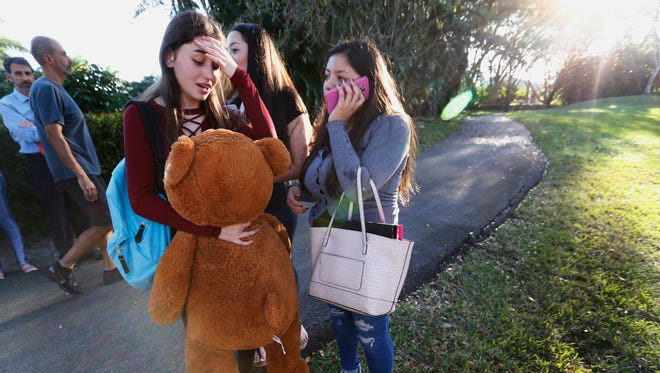 Students wait to be picked up after a shooting at Marjory Stoneman Douglas High School.