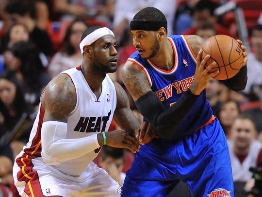 New York Knicks forward Carmelo Anthony (7) is pressured by Miami Heat forward LeBron James (6).