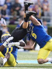 Delaware defensive back Anthony Jackson (left) and linebacker Charles Bell tackle James Madison quarterback Bryan Schor in the second quarter at Delaware Stadium. Bell was injured on the play and did not return.