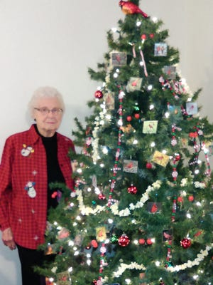 Ivy Sorenson, 103, poses next to the tree she decorated with garlands and Christmas ornaments she made.