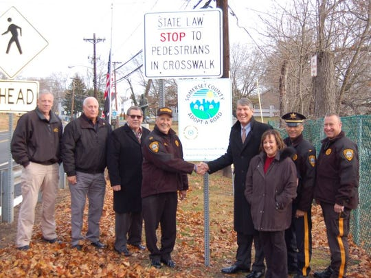 Joining in the launch of the Sheriff's Adopt-A-Road program in Raritan Borough are (from left) Col. Richard Borden, Col. Roy Gandolfe, Deputy Warden Roger Delin, Sheriff Frank Provenzano, Mayor Charles McMullin, Council President Denise Carra, Lt. Steve SanAntonio and Sheriff's Officer Dave Daneker.