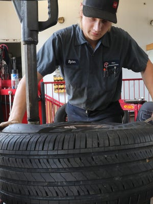 Tire Connection worker Dylan Brooks mounts a new tire on a rim Tuesday in Green.