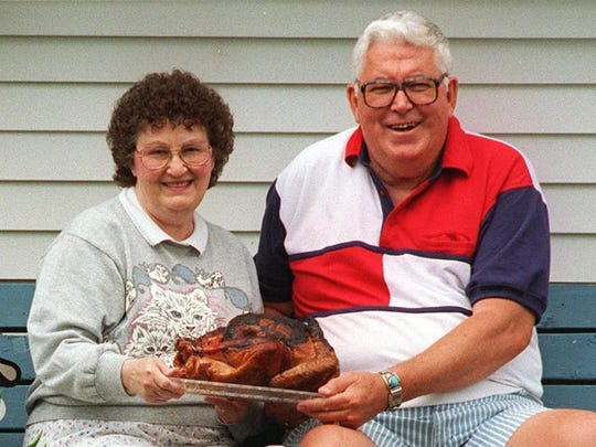 June and Slim Betterley display a charcoaled turkey they prepared with their own homemade sauce outside their home in Honeoye, Ontario County.