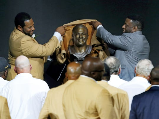 Former NFL player Jerome Bettis, left, unveils his Hall of Fame bust with his presenter and brother, John Bettis III, during inductions at the Pro Football Hall of Fame on Saturday in Canton, Ohio.