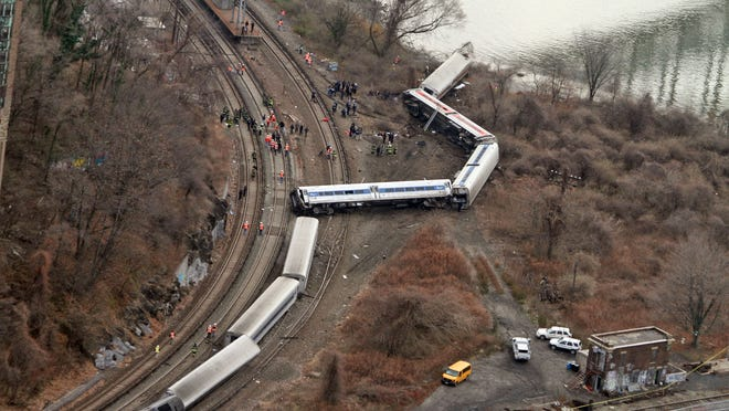 Emergency personnel work at the scene of a Metro-North train that derailed just north of the Spuyten Duyvil station in the Bronx Dec. 1, 2013. Four people were killed and dozens more were injured when the Manhattan bound train derailed shortly after 7 a.m.