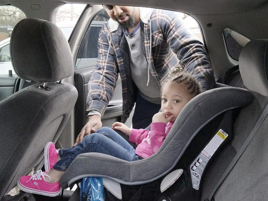 Lavonte Dell's daughter Lauren, 3, in her new car seat. The car seat is pink and gray - Lauren loves pink.