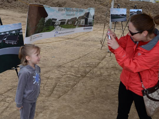 Ashley Grace snaps a photograph of her daughter Gwendolyn, 5, in front of a mock-up of the William A. Pearson Elementary during its May 7 groundbreaking. Gwendolyn will attend first grade at the school once it opens in 2017.