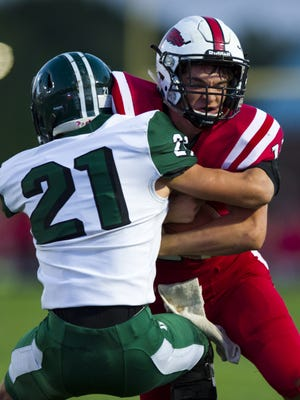 New Palestine High School junior Zach Neligh (11) grimaces as he's hit by Pendleton Heights High School junior Jarod Miller (21) running the ball out of the backfield during the first half of an IHSAA high school football game at New Palestine High School, Friday, September 15, 2017.