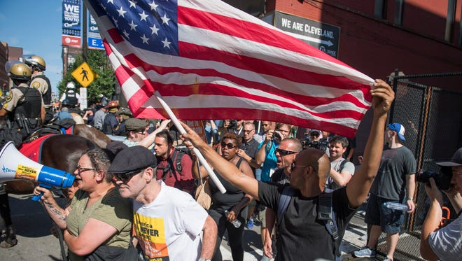 Protester yell and follow Cleveland Police arresting a woman during a protest march involving people planning to burn the American flag outside the 2016 Republican National Convention in Cleveland July 20, 2016.