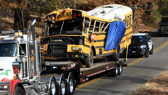 Chattanooga Police vehicles escort a flatbed truck hauling a crushed school bus from the scene Monday on Talley Road in Chattanooga. Six Woodmore Elementary School students were killed when the bus crashed Monday afternoon.