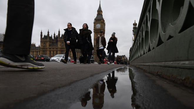 Commuters walks over Westminster bridge by the Houses of Parliament in central London on March 29, 2017.
