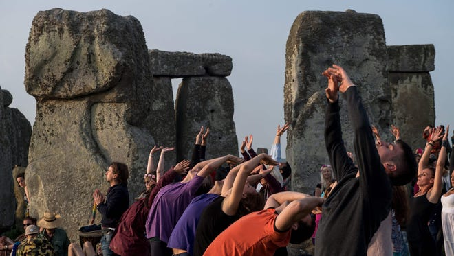 Revellers practice yoga as the sun rises during Summer Solstice at Stonehenge in Wiltshire, England. The festival, which dates back thousands of years, celebrates the longest day of the year when the sun is at its maximum elevation. Modern druids and people gather at Stonehenge every year to see the sun rise on the first morning of summer.