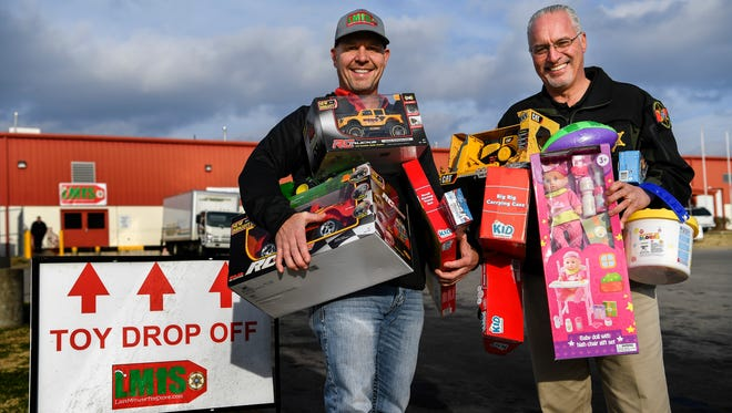 Pastor Dale Robble, left and Sheriff Daron Hall stand with arms full of toys outside the Last Minute Toy Store in Nashville, Tenn., Thursday, Dec. 7, 2017.