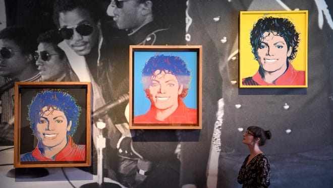 A woman poses next to Andy Warhol's works 'Michael Jackson' during a press preview of the exhibition 'Michael Jackson: On the Wall' at the National Portrait Gallery in London, Britain, June 27, 2018.