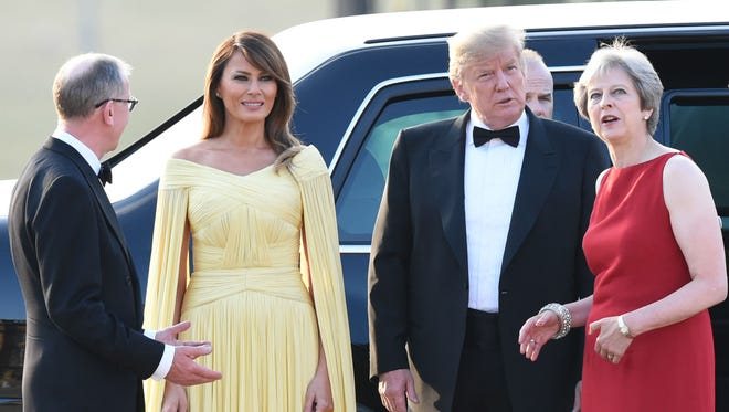 President Donald Trump and first lady Melania Trump are welcomed by British Prime Minister Theresa May and her husband Philip May as they arrive for a black-tie dinner with business leaders at Blenheim Palace, west of London, on Thursday.