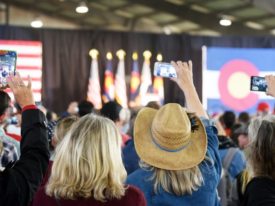 "Three women snap photos as Donald Trump speaks at a campaign rally in Colorado Springs, Colo., on Oct. 18, 2016. Several times, Trump urged the crowd to turn around and face the media behind them and yell, ""tell the truth."""