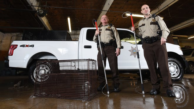 Coshocton County Dog Warden Rusty Dreher, right, and Deputy Dog Warden Steve Walsh with some of their equipment. Not pictured is a can of smelly cat food that lures dogs into traps like a charm.