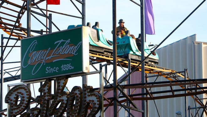 """Firefighters reach three children stranded on the """"Python"""" roller coaster at Coney Island Sunday evening."""