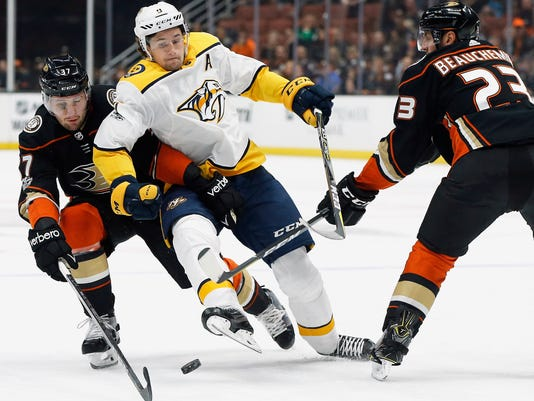 Nashville Predators left wing Filip Forsberg, center, competes for the puck with Anaheim Ducks left wing Nick Ritchie, left, and defenseman Francois Beauchemin during the first period of an NHL hockey game in Anaheim, Calif., Friday, Nov. 3, 2017. (AP Photo/Alex Gallardo)